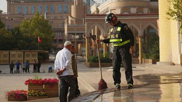 Policial chinês limpando escadas de mesquita na cidade de Kashgar