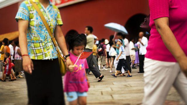 Niña con su madre en una plaza en Pekín
