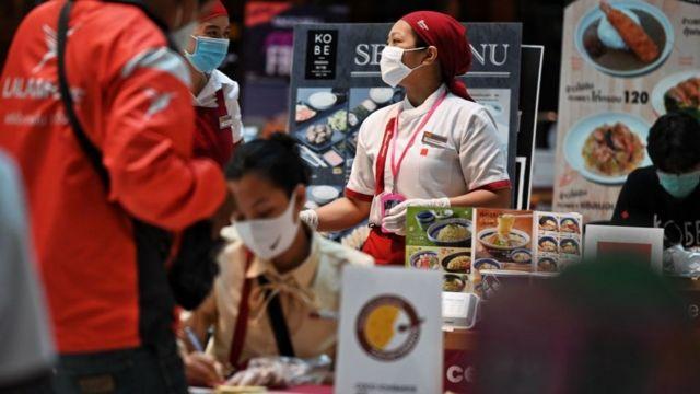 Nhân viên một nhà hàng bán thức ăn mang đi tại Bangkok tất bật khi số đơn đặt hàng tăng vọt trong ngày đầu của tình trạng khẩn cấp ở Thái Lan