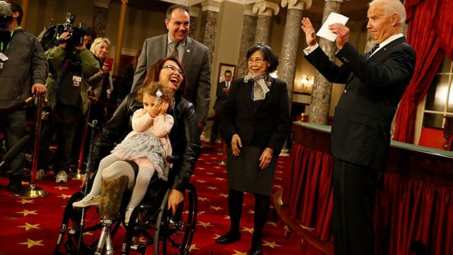 US Sen Tammy Duckworth participates in a re-enacted swearing-in with Joe Biden in January 2017