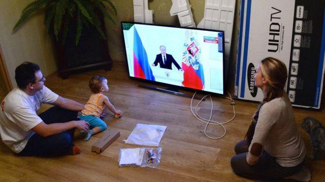 Молодая семья смотрит послание Владимира Путина Федеральному собранию