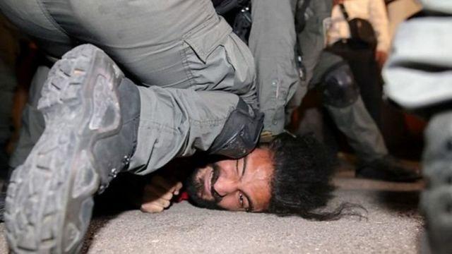 یکی از فعالان شناخته شده فلسطینی در تظاهرات روز ۴ ماه مه در حالی که افسر پلیس اسرائیل روی صورتش زانو زده است
