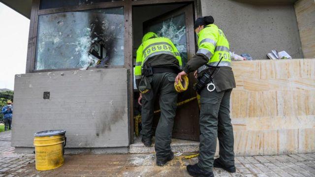Polcías revisan un CAI que fue atacado por manifestantes en Bogotá.