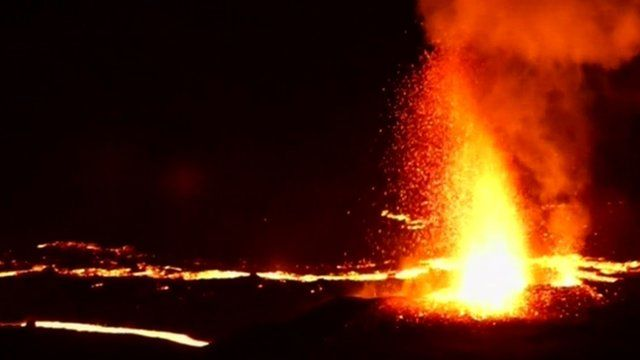 Lava spewing from volcano at night