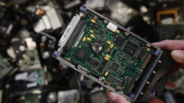 A worker holds a discarded hard drive from an old computer that will be stripped down to its parts in Berlin, Germany