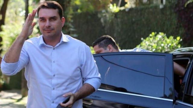 Flávio Bolsonaro posa para foto enquanto sai de carro