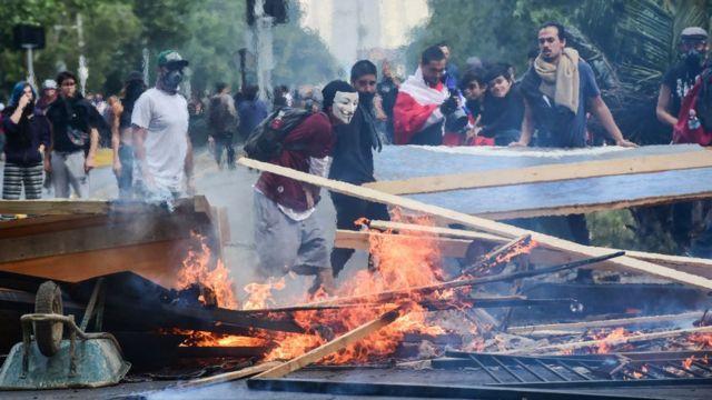 manifestantes ante maderas en llamas en Santiago de Chile