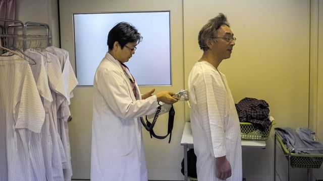 Un doctor preparara un paciente para hacerle una prueba por radiación en Fukushima.