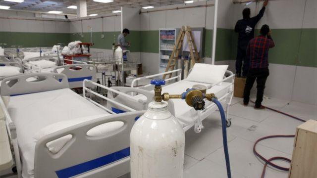 Trabajadores instalan un hospital de emergencia en un centro comercial en Teherán, India.