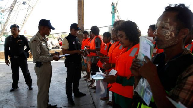 hai Marine police officers inspect documents and work permits from Myanmar migrant fishermen at a fishing port in Samut Sakhon province, Thailand, 19 March 2018