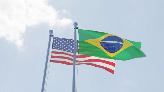 Bandeiras dos EUA e do Brasil sob o céu