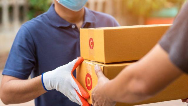 Homem entregando duas caixas para outro homem