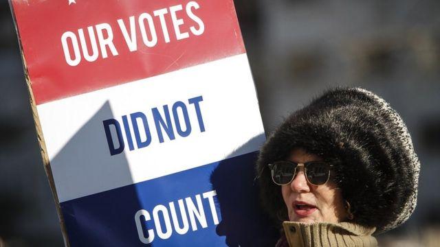 Una mujer protesta con una pancarta después de que el colegio electoral le diera la victoria a Donald Trurmp