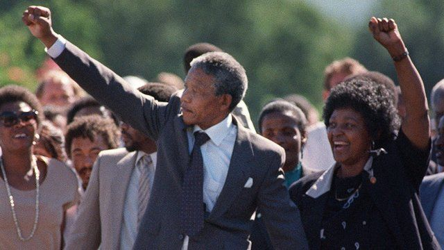 Nelson Mandela and Winnie Mandela raise their arms on his release from prison