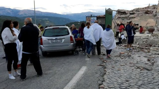 People stand along a road following a quake in Amatrice