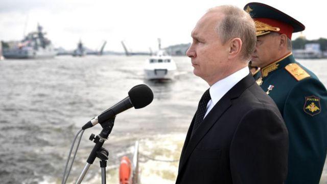 Putin junto a un militar y frente a unos barcos
