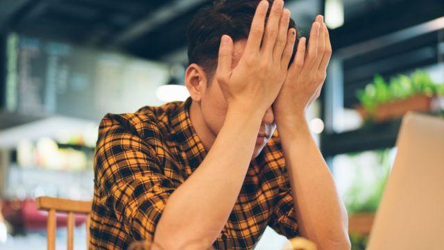 Un chico tapándose la cara
