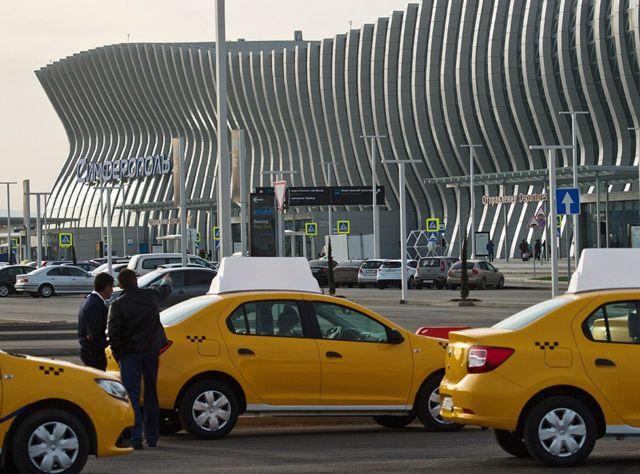 SIMFEROPOL, RUSSIA - APRIL 16, 2018: Taxi cars outside the new passenger terminal building at the Simferopol Airport in Simferopol, Crimea, Russia
