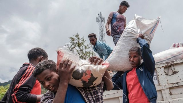Civilians displaced by fighting in northern Ethiopia offloading food and supplies from a truck at a school in Dessie, Ethiopia, on August 23, 2021