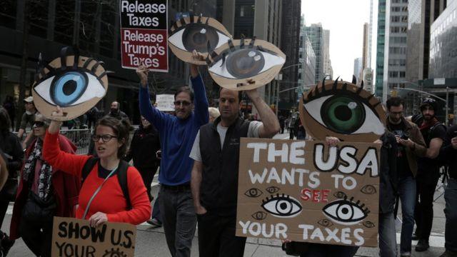 Manifestantes seguram cartazes em rua de Nova York