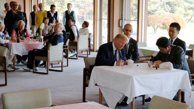 特朗普(前左)與安倍晉三(前右)在埼玉縣霞關鄉村俱樂部餐廳內於鴨舌帽上簽名(5/11/2017)