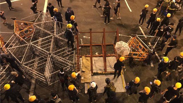 示威者集結做路障,从远处运来更多的铁栏。