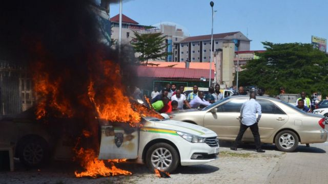 People stand next to a police car that has set alight