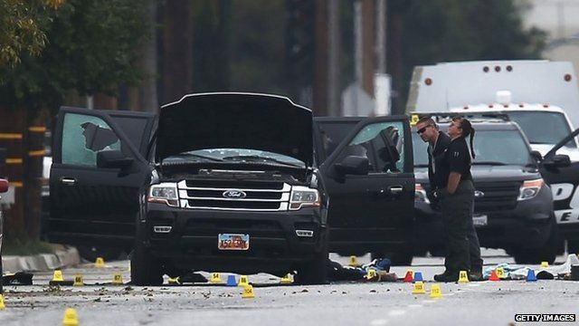 Law enforcement officials continue their investigation around a vehicle at the scene of Wednesday's attack