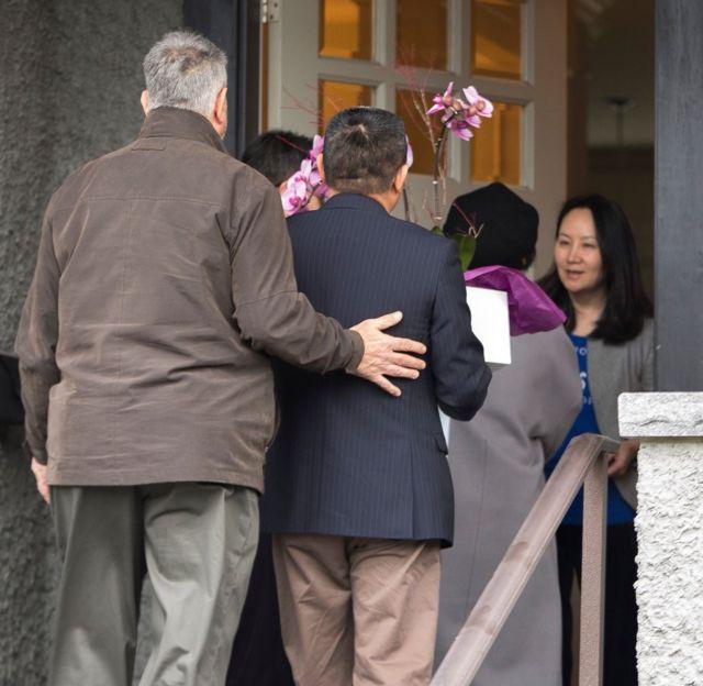 孟晚舟在门口迎接看望她的客人。