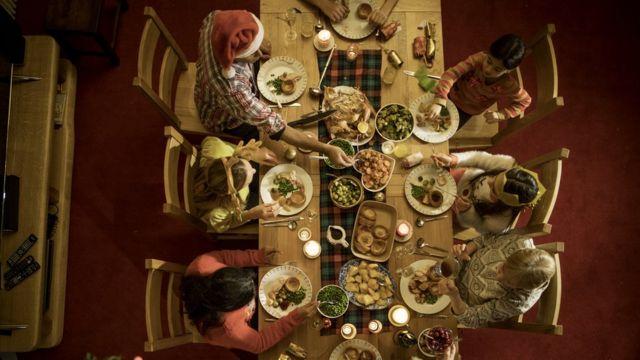 Mesa com ceia de natal e família sentada ao redor vista do alto