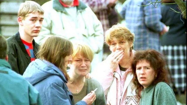 Imagem mostra pessoas chorando após massacre de crianças em escola na Escócia, em 13/03/1996