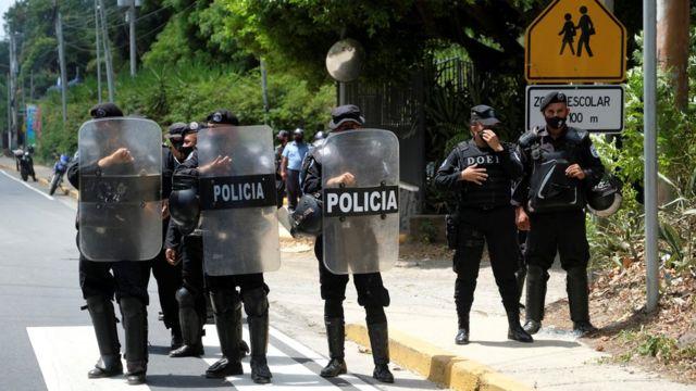 Des policiers nicaraguayens se tiennent en formation et bloquent les journalistes travaillant devant la maison de la dirigeante de l'opposition Cristiana Chamorro.