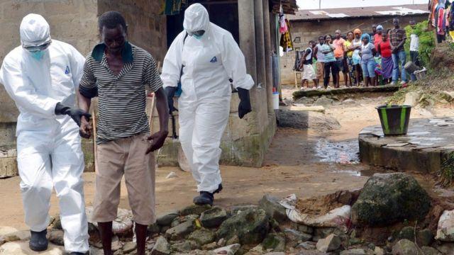 Un hombre infectado con el virus del ébola es trasladado al hospital por sanitarios en buzos de seguridad.