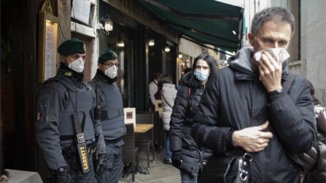 Police and members of the public wear protective face masks during the Carnival in Venice, Italy, 23 February 2020.