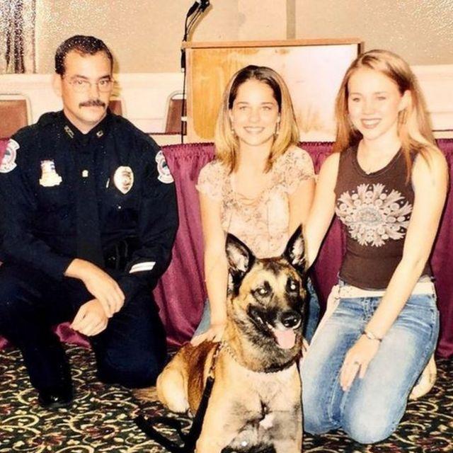 Kara with a policeman, another girl and a German shepherd dog