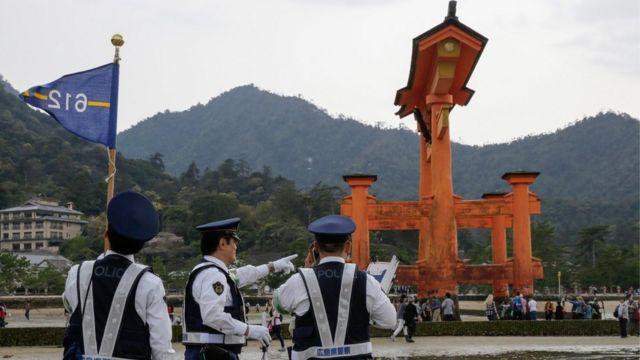 Japanese policemen check security near a wooden gate in Hatsukaichi, Hiroshima