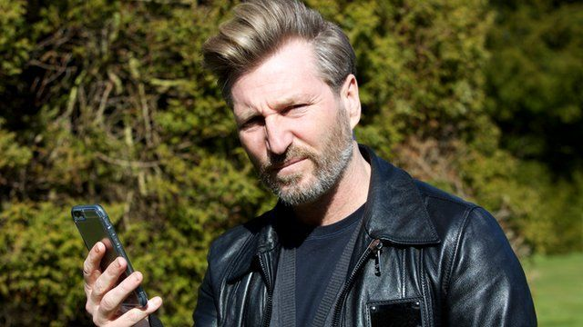 Robbie Savage with a smart phone