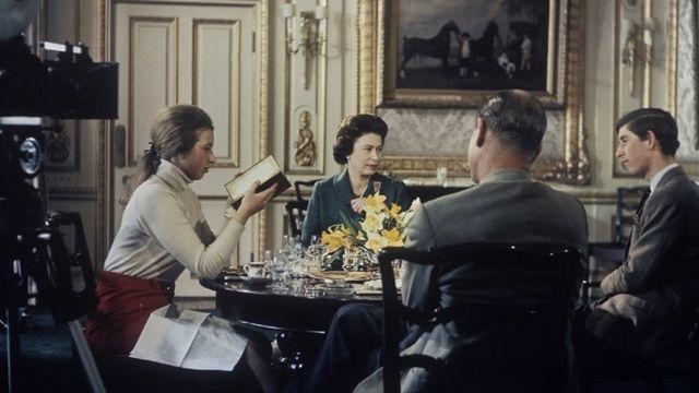 A princesa Anne, a rainha Elizabeth, o príncipe Charles e o príncipe Philip ao redor de uma mesa durante a gravação de um documentário