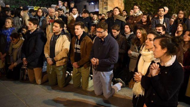 Personas rezan en los alrededores de Notre Dame