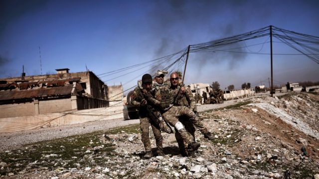 Members of Iraq's elite Rapid Response Division carry a wounded comrade in the northern city of Mosul, as Iraqi forces continue the offensive to retake the city's western half from Islamic State (IS) group fighters, on February 25, 2017