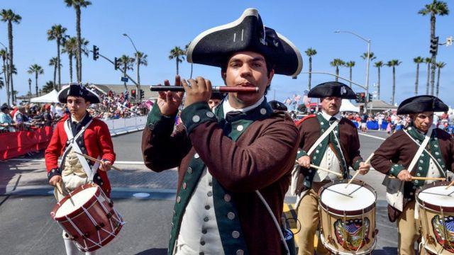 Hombres vestidos como collonos revolucionarios en un desfile del 4 de julio en Estados Unidos