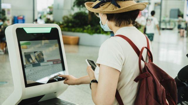 Una mujer realiza una facturación en una máquina de un aeropuerto.