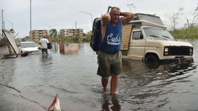 Un hombre carga su maleta en una calle inundada de Puerto Rico.