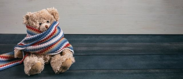 Cute teddy bear with colorful scarf sitting on blue wooden background
