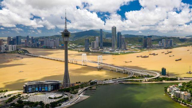 从澳门半岛以无人机俯瞰澳门旅游塔(中)与广东珠海横琴岛(后)(新华社图片18/6/2020)