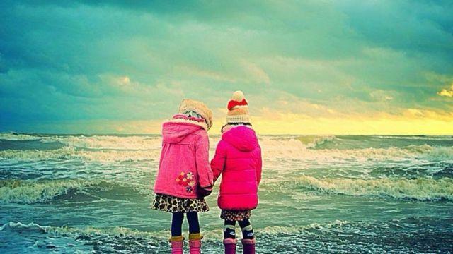 Niñas en la playa con parkas.