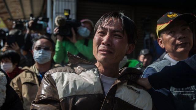 住民家族への現地説明を聞きながら涙を流す男性