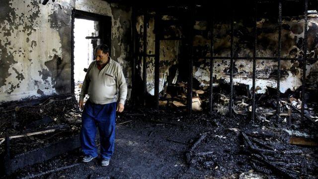 Житель городка Барда в сгоревшем от ракеты доме