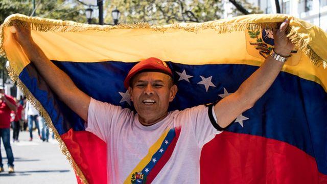 Un hombre ondea la bandera venezolana