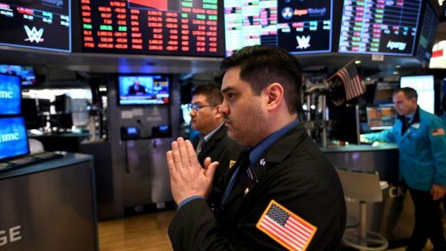 Un hombre con las manos rezando en la bolsa de Nueva York.